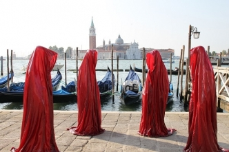 People with red cloaks on a quay in Venice