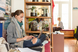 Student with laptop in a common room