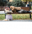 Homeless man lying on a bench in the park